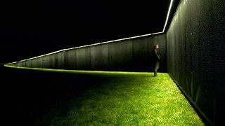man stands at vietnam memorial wall replica