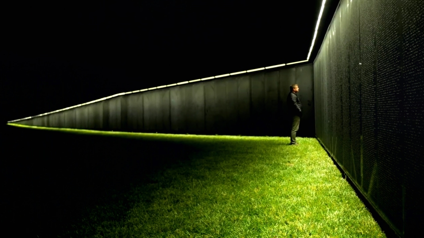 man stands at vietnam memorial wall replica