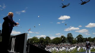 President Donald Trump applauds as Army helicopters fly overand West Point cadets toss their caps into the air at the end of commencement ceremonies on the parade field, at the United States Military Academy in West Point, N.Y., Saturday, June 13, 2020.