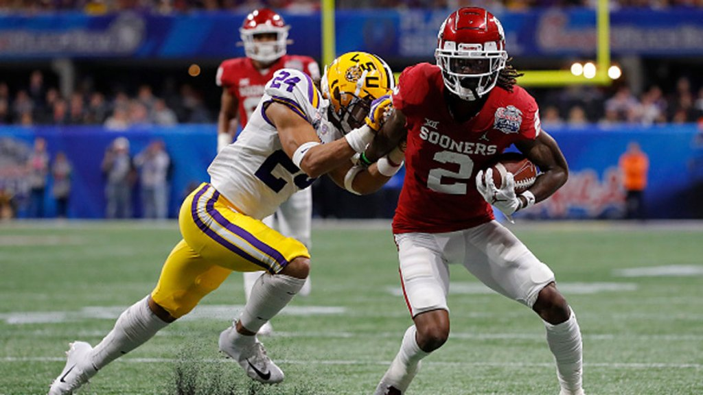 Wide receiver CeeDee Lamb #2 of the Oklahoma Sooners carries the ball against Derek Stingley Jr. #24 of the LSU Tigers during the Chick-fil-A Peach Bowl at Mercedes-Benz Stadium on December 28, 2019 in Atlanta, Georgia.
