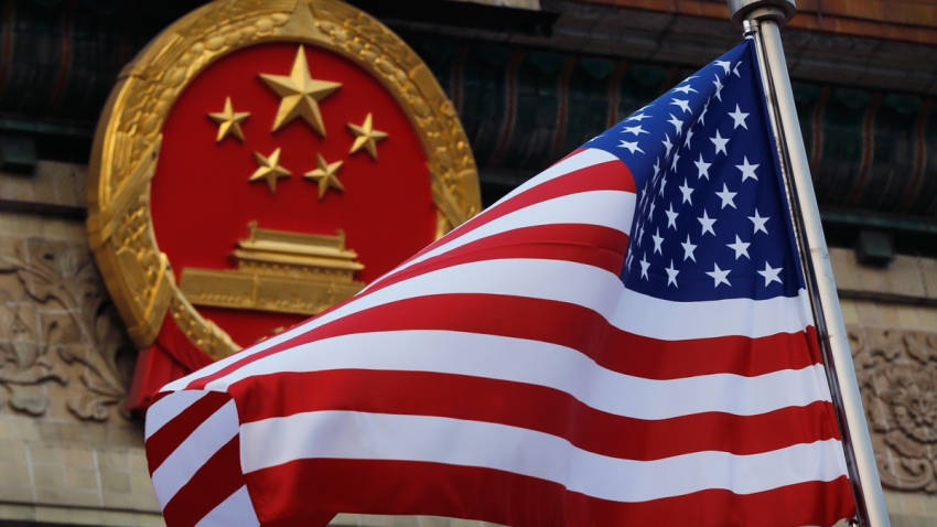 In this Nov. 9, 2017, file photo, an American flag is flown next to the Chinese national emblem during a welcome ceremony for visiting U.S. President Donald Trump outside the Great Hall of the People in Beijing.