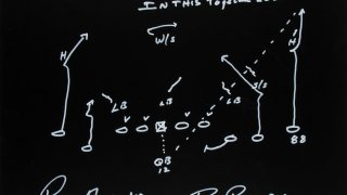 """Roger Staubach captured the design of the famous Hail Mary play in chalk. He and receiver Drew Pearson, who caught the pass, signed the piece for the """"In This Together"""" charity auction, benefiting the North Texas Food Bank."""