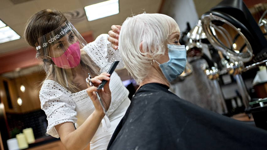 In this May 29, 2020, file photo, a stylist wearing a protective face shield and mask cuts a customers hair at a salon in Arlington, Virginia.