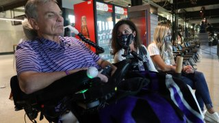 Jim Hilliard, Tamara Hilliard and Kat Minnerly watch the Colorado Rockies play against the Texas Rangers in an exhibition baseball game Tuesday, July 21, 2020 in Arlington, Texas. The Hilliards are the parents of Rockies left fielder Sam Hilliard and Minnerly is his fiancee.