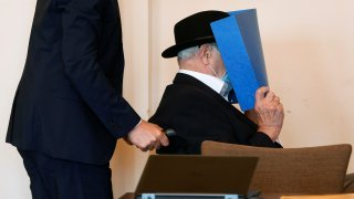 Bruno Dey, a former SS-watchman at the Stutthof concentration camp, hides his face behind a folder as he arrives on a wheelchair for a hearing in his trial on July 23, 2020 in Hamburg, northern Germany.