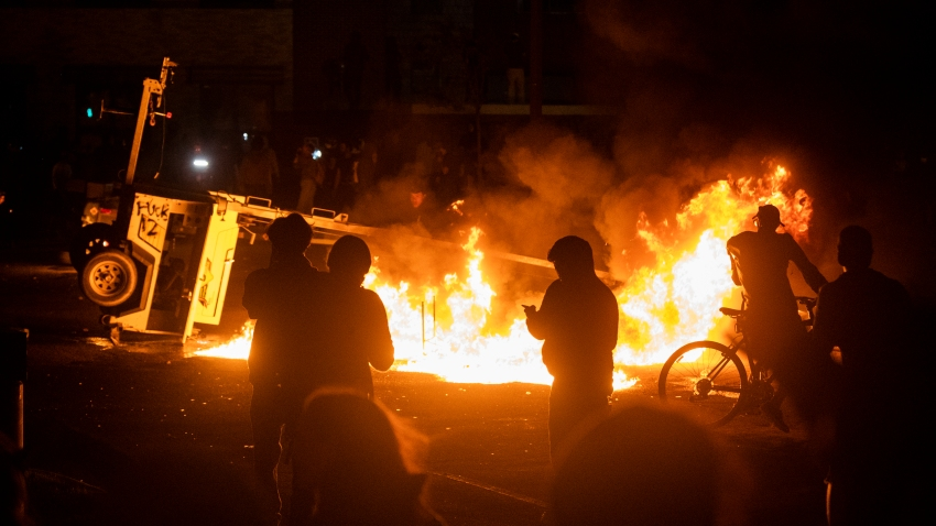 MINNEAPOLIS, MN - MAY 28: A surveillance camera burns in the parking lot of the Third Police Precinct on May 28, 2020 in Minneapolis, Minnesota. As unrest continues after the death of George Floyd police abandoned the precinct building, allowing protesters to set fire to it.