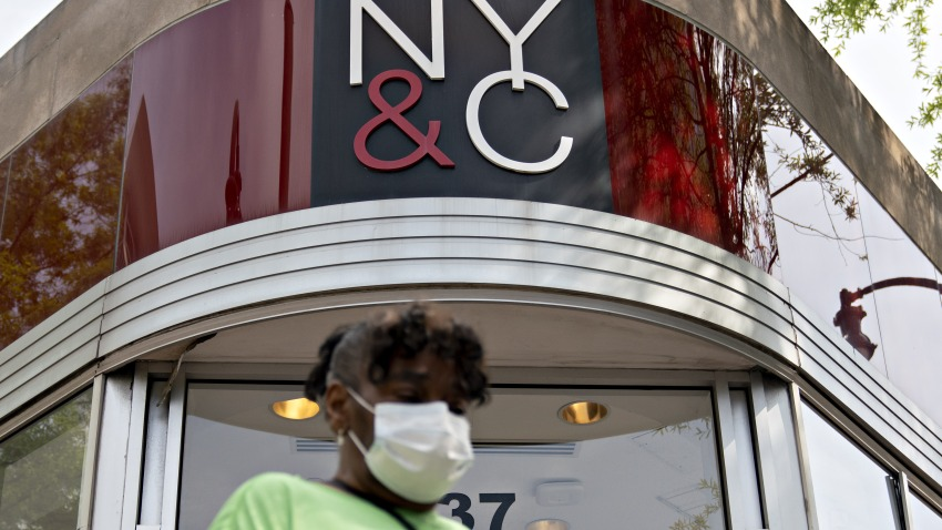 A pedestrian wearing a protective mask walks past a temporarily closed New York & Co. store in Silver Spring, Maryland, U.S., on Friday, June 5, 2020.