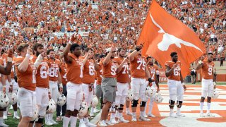 """Texas Longhorn players salute the crowd with """"The Eyes of Texas"""" after 13 - 10 loss to The Oklahoma State Cowboys on Oct. 21, 2017 at Darrell K Royal-Texas Memorial Stadium in Austin, Texas."""