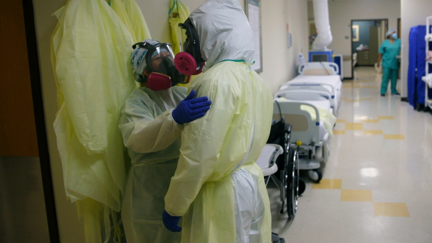In this July 29, 2020, file photo, medical personnel talk as they care for COVID-19 patients at DHR Health, in McAllen, Texas. Texas surpassed 10,000 confirmed coronavirus deaths Monday as the lingering toll of a massive summer outbreak continues, and health experts worry that recent encouraging trends could be fragile as schools begin reopening for 5 million students across the state.