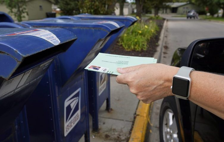 A person drops applications for mail-in-ballots into a mail box in Omaha, Neb