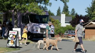 Bobby Price, right, and Catherine Vogt, center, walk with Catherine's daughter Avery, 8, and their dogs after ordering food and drinks from the YS Street Food and Dreamy Drinks food trucks, Monday, Aug. 10, 2020, near the suburb of Lynnwood, Wash.