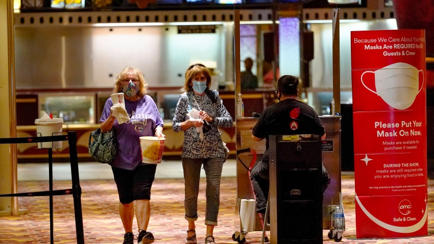 Two women pass by the ticket checkpoint at an AMC theater