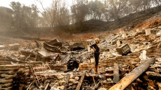 Pam, who declined to give a last name, examines the remains of her partner's Vacaville, Calif., home