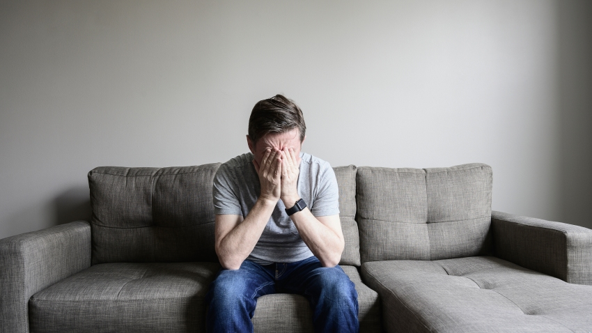 Depressed mature man sitting on couch.