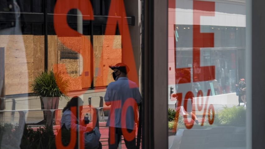 People wearing protective masks walk past an H&M store window display in San Francisco, California, U.S., on Thursday, Aug. 6, 2020. U.S. consumer sentiment extended its slide in late July as the resurgent coronavirus led to renewed business closings and layoffs, adding to signs the economic recovery is stalling.