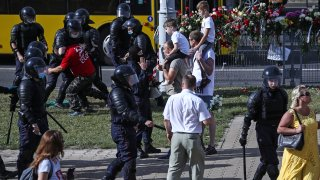 Riot police detain a man participating in a memorial event for a person killed in a clash with law enforcement officers during a protest against the results of the 2020 Belarusian presidential election