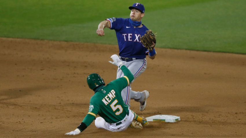 Nick Solak #15 of the Texas Rangers gets out Tony Kemp #5 of the Oakland Athletics at second base and turns a double play in the bottom of the eighth inning at Oakland-Alameda County Coliseum on August 04, 2020 in Oakland, California.