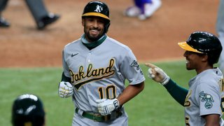 Marcus Semien #10 of the Oakland Athletics celebrates with Tony Kemp #5 of the Oakland Athletics after hitting a two-run home run against the Texas Rangers in the top of the fifth inning at Globe Life Field on Aug. 25, 2020 in Arlington, Texas.