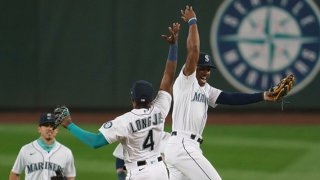 Kyle Lewis #1 (R), Shed Long Jr. #4 and Sam Haggerty #28 of the Seattle Mariners celebrate after a game against the Texas Rangers at T-Mobile Park on August, 22, 2020 in Seattle, Washington. The Mariners won 10-1.