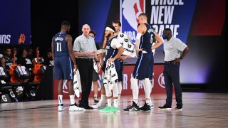 The Dallas Mavericks huddle up during a game against the Phoenix Suns on August 2, 2020 at Visa Athletic Center at ESPN Wide World Of Sports Complex in Orlando, Florida.