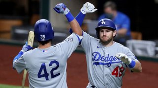 """Max Muncy #42 of the Los Angeles Dodgers celebrates with Cody Bellinger #42 of the Los Angeles Dodgers after hitting a three-run home run against the Texas Rangers in the top of the seventh inning at Globe Life Field on Aug. 29, 2020 in Arlington, Texas. All players are wearing #42 in honor of Jackie Robinson Day. The day honoring Jackie Robinson, traditionally held on April 15, was rescheduled due to the COVID-19 pandemic."""""""