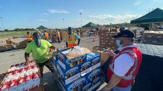 Men stand outside next to palets of food to be donated.