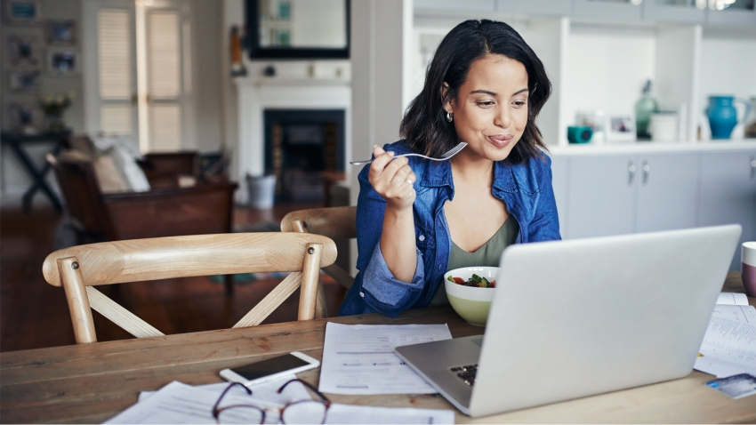 young woman eating while working from home on laptop