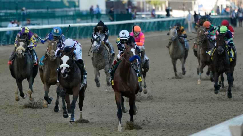 Multiple jockeys in a horse race riding in direction of the camera