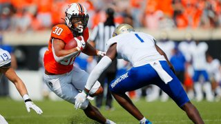 Running back Chuba Hubbard #30 of the Oklahoma State Cowboys tries to make a cut against safety Kendarin Ray #1 of the Tulsa Golden Hurricanes in the third quarter on Sept. 19, 2020 at Boone Pickens Stadium in Stillwater, Oklahoma.