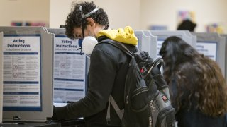 A voter wearing a respiratory mask casts a ballot at a polling station in City Hall in San Francisco, Calif.