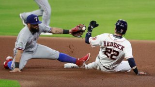 Josh Reddick #22 of the Houston Astros steals second base in the fourth inning against a late tag from Rougned Odor #12 of the Texas Rangers at Minute Maid Park on September 15, 2020 in Houston, Texas.