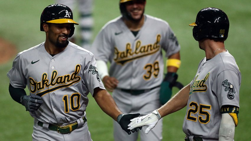 Marcus Semien #10 of the Oakland Athletics celebrates a three-run homerun with Stephen Piscotty #25 against the Texas Rangers in the fifth inning at Globe Life Field on Sept. 12, 2020 in Arlington, Texas.