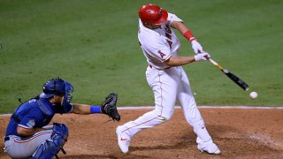 Mike Trout #27 of the Los Angeles Angels hits an RBI single in front of Jeff Mathis #2 of the Texas Rangers, to take a 4-3 lead, during the eighth inning at Angel Stadium of Anaheim on Sept. 19, 2020 in Anaheim, California.