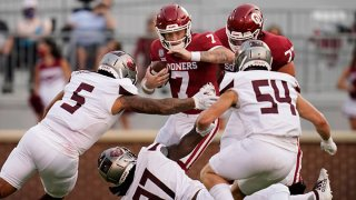 Oklahoma quarterback Spencer Rattler #7 carries against Missouri State defenders Ferrin Manulelua #5), Michael Pope #97 and Von Young #54 in the first half of an NCAA college football game on Sept. 12, 2020, in Norman, Oklahoma.