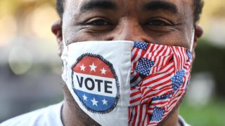 A voter smiles behind a mask.