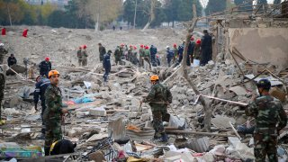 Soldiers and firefighters search for survivors in a residential area that was hit by rocket fire overnight by Armenian forces, early Saturday, Oct. 17, 2020, in Gyanga