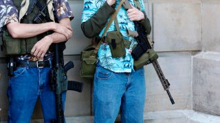 """Armed protesters demonstrate during the Michigan Conservative Coalition organized """"Operation Haircut"""" outside the Michigan State Capitol"""