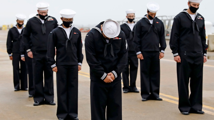 Sailors of the USS Cole bow their heads during a benediction following a remembrance ceremony commemorating the 20th anniversary of the attack on USS Cole