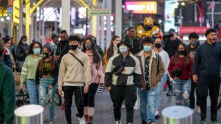 People with and without masks walk in Times Square
