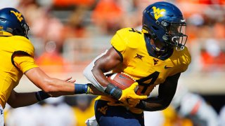 Running back Leddie Brown #4 of the West Virginia Mountaineers takes a hand-off from quarterback Jarret Doege #2 against the Oklahoma State Cowboys in the first quarter on Sept. 26, 2020 at Boone Pickens Stadium in Stillwater, Oklahoma. OSU won 27-13.