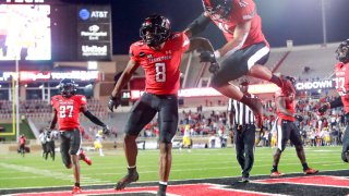 Cornerback Zech McPhearson #8 of the Texas Tech Red Raiders celebrates with linebacker Jacob Morgenstern #41 after running an interception for a touchdown during the second half of the college football game against the West Virginia Mountaineers on October 24, 2020 at Jones AT&T Stadium in Lubbock, Texas.