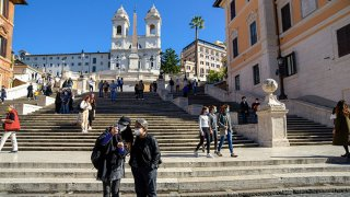 Tourists wearing face masks take a selfie in Piazza di Spagna. In Italy, the increase in coronavirus is over 10,000 a day and has prompted the government to oblige protective masks on the streets and to take other measures to contain the pandemic.