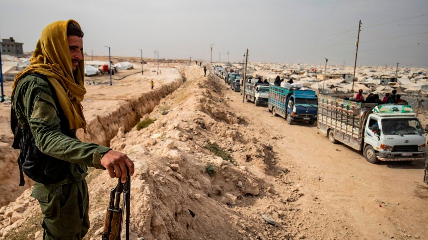 A Kurdish fighter looks on as a convoy of trucks transporting Syrian women and children suspected of being related to Islamic State (IS) group leaves the Kurdish-run al-Hol camp, after being released to return to their homes, in the al-Hasakeh governorate in northeastern Syria, on October 28, 2020. Earlier this week, an Oregon man was indicted Thursday after authorities said he supported the Islamic State group by distributing articles on how to kill and maim with a knife and encouraging readers to carry out attacks.