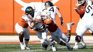 DeMarvion Overshown #0 of the Texas Longhorns sacks Jarret Doege #2 of the West Virginia Mountaineers in the third quarter at Darrell K Royal-Texas Memorial Stadium on Nov. 7, 2020 in Austin, Texas.