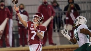 Oklahoma quarterback Spencer Rattler (7) passes under pressure from Baylor linebacker William Bradley-King (99) in the first half of an NCAA college football game Saturday, Dec. 5, 2020, in Norman, Okla. (AP Photo/Sue Ogrocki)