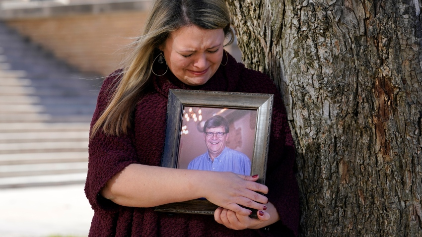 Katie Riggs Maxwell begins to cry as she hugs a portrait of her father Mark Riggs while posing for a photo, Wednesday, Dec. 16, 2020, on the campus of Abilene Christian University in Abilene, Texas. Mark Riggs, who was a professor at the school, passed away last Monday of COVID-19.