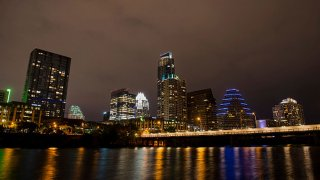 Buildings stand in the downtown skyline at night past the Colorado River in Austin, Texas, U.S., on Saturday, April 4, 2015.