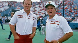 Heads coaches Barry Switzer of the University of Oklahoma (L) and Fred Akers of the University of Texas (R) looks on prior to there NCAA football game October 11, 1986 at the Cotton Bowl in Dallas, Texas.
