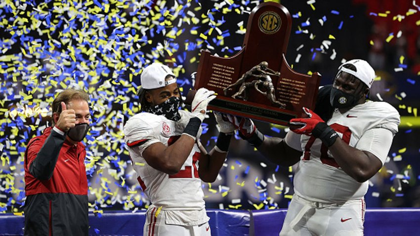 Head coach Nick Saban, Najee Harris #22, and Alex Leatherwood #70 of the Alabama Crimson Tide hold up the trophy as they celebrate their 52-46 win over the Florida Gators in the SEC Championship at Mercedes-Benz Stadium on Dec. 19, 2020 in Atlanta, Georgia.
