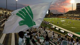 Supporters of the North Texas Mean Green wave a team flag as they take on the Houston Baptist Huskies during a game at Apogee Stadium on Sept. 5, 2020 in Denton, Texas.